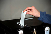 Woman putting her ballot paper into the ballot box at a  polling station.