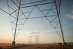 Clouds at sunrise over the Antelope Valley in Southern California, high voltage power line pylon tower.