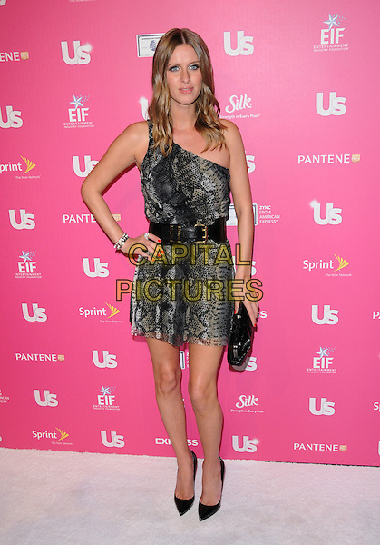 NICKY HILTON.The Annual US Weekly Hot Hollywood Event held at The Colony in Hollywood, California, USA..November 18th, 2010.full length gray snakeskin print one shoulder dress clutch bag shoes hand on hip belt grey.CAP/RKE/DVS.©DVS/RockinExposures/Capital Pictures.