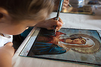 Romania. Iași County. Iasi. A girl is painting a representation of the Blessed Virgin Mary on a glass <br /> in the Orthodox Church &quot;Saint Nektarios&quot;. Mary, also known as Saint Mary or the Blessed Virgin Mary, is identified in the Bible as the mother of Jesus. Iași (also referred to as Iasi, Jassy or Iassy) is the largest city in eastern Romania and the seat of Iași County. Located in the Moldavia region, Iași has traditionally been one of the leading centres of Romanian social, cultural, and artistic life. The city was the capital of the Principality of Moldavia from 1564 to 1859, then of the United Principalities from 1859 to 1862, and the capital of Romania from 1916 to 1918. 6.06.15 &copy; 2015 Didier Ruef