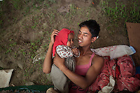 Rajib, 20 plays with his three months old son Rajib at Shila Porbot, outskirts of Kathmandu, Nepal. Promila and Rajib lost their home in last month's Nepal earthquake and now they are living in a temporary house in the bank of a river. May 8, 2015