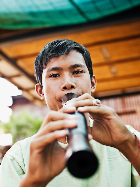 Cambodia Living Arts student Yim Sokung plays a Sralai. Yim  is a music student in the classical and folk dance class of Master Ieng Sithul. Phnom Penh, Cambodia...The sralai is a Khmer (Cambodian) musical instrument. It is the only wind instrument in the pinpeat, a classical ensemble of wind and percussion instruments. Its quadruple reed is made of palm leaf, and its body has a slightly conical bore. Its cousin, the Western oboe, has a double reed and a conical bore. The pinpeat instruments tune to the sralai's pitch. The player must learn circular breathing to play continuously without stopping for breath...Cambodian Living Arts works to support the revival of traditional Khmer performing arts and to inspire contemporary artistic expression. CLA supports arts education, mentorship, networking opportunities, education, career development, and income generating projects for master performing artists who survived the Khmer Rouge as well as the next generation of student artists...