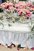 Bed of roses, literally, bouquets on and under a big bed with white bedding and wrought iron footboard