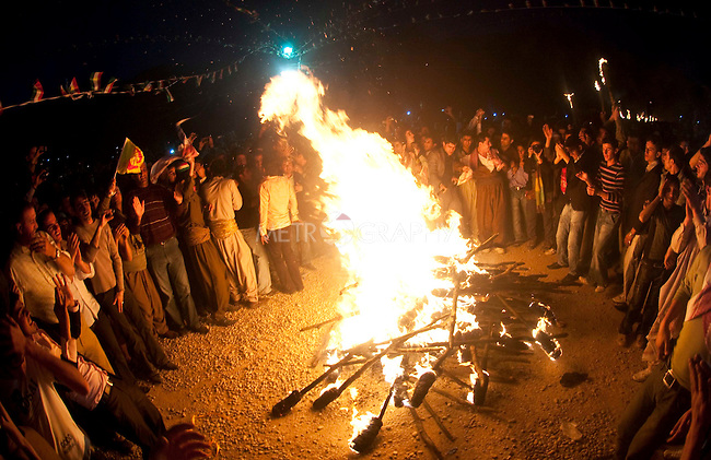 AKRE, IRAQ:  Kurdish men dance around a bonfire made of used torches...Newroz, celebrated across the world on the vernal equinox, is the official beginning of the Kurdish calendar and the first day of spring.  Kurds celebrate Newroz on March 20th and 21st by lighting fires and performing traditional dances...Photo by Kamaran Najm/ Metrography
