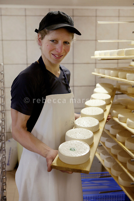Regine Misillier poses for the photographer with a tray of reblochon cheese in the dairy, Ferme le Tavaillon, Le Grand Bornand, France, 16 February 2012.