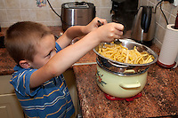 Young Polish boy age 6 helping himself to some freshly cooked yellow beans. Zawady Central Poland