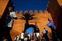 """People walk through Bab el Had gates of Rabat's Medina September 21, 2014. Behind walls of Medina and Kasbah of the Oudayas, ancient neighbourhoods of Morocco's capital, labyrinths of small alleys, colourful buildings and street markets offer a glimpse into city's rich history. Rabat was recently listed by UNESCO as a World Heritage Site and suggested as a """"must see"""" destination by major media outlets and tourist agencies.  REUTERS/Damir Sagolj (MOROCCO)"""