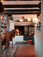 A large open fireplace and candlelight evokes a Christmas atmosphere in this country kitchen