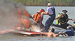 """Chris Oliver Sr. is pulled from the cockpit of his burning 2.5 liter modified race boat """"Every Penny"""" as rescuers splash water onto the fire after the boat engine ignited during a race at the 2010 Thunder on the Narrows."""