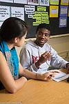 Education HIgh School female teacher listening to male student talking, in classroom