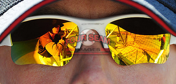 Jordan Weems and the batting cage are reflected in the sunglasses Greenville Drive hitting coach Darren Fenster before a game against the Lakewood BlueClaws on April 6, 2012, at Fluor Field at the West End in Greenville, South Carolina. (Tom Priddy/Four Seam Images)