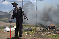 KENYA, Nairobi, city centre, waste picker burns garbage and cable insulation of electric cable on the road to collect copper
