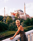 TURKEY, Istanbul, smiling lady looking away with the Aya Sofya mosque in the background