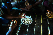 Villagers share a plate of sticky rice after coming back from fishing in Damin Naung village in Pyapon district of Myanmar.