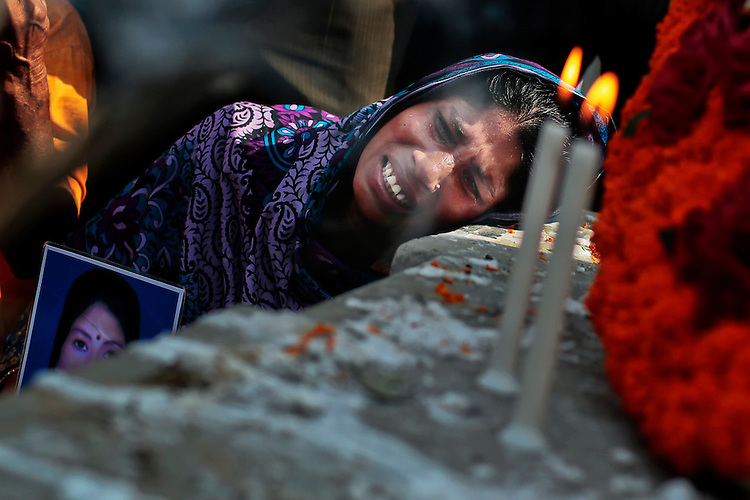 Bangladeshi relative of a victim cries in front of a monument erected in memory of the victims of Rana Plaza building collapse as they gather at the spot on its second anniversary in Savar, near Dhaka, Bangladesh.