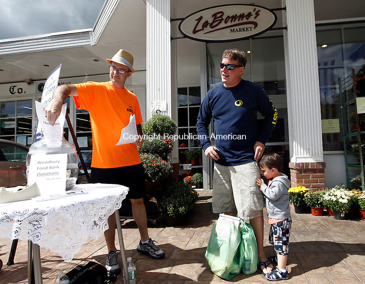 Woodbury, CT- 30 August 2014-083014CM02- Richard Miska, left, with King Solomon's Lodge No. 7 of Woodbury, collects a donation from Ryan Sprole and his son, Graham Sprole, 2, of Woodbury outside LaBonne's Market in Woodbury on Saturday.  Members of the lodge were  collecting donations of food for the Woodbury Food Bank.    Christopher Massa Republican-American