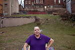 """Karen Snyder, 47, enjoys a cigarette during a break from the nearby mental health facility she works at in downtown Braddock, Pennsylvania, February 2012. Karen moved back to Braddock from California a few years ago. Her mother grew up in Braddock and her great grandfather worked at the steel mill. """"I like Braddock,"""" she said. """"I wis it could come back to life. They just knocked four buildings down."""""""