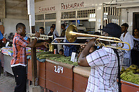 A street band plays and collect tips between vegetable stalls in the Central Market of Paramaribo. This is a tradition in Suriname and the bands plays at different locations, places before  important days, festive start.....End of year 2010 celebrations on the streets of Paramaribo. Suriname is one of biggest consumer in South America that using firecrackers, fireworks ( also locally known as pagara ) for celebrations, especially for end of every years and also beginning of every new Chinese Years.