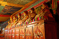 Old Buddhist statues of the Gelugpa Yellow-Hat order line the wall at Ngagpa College, Drepung Monastery, Lhasa, Tibet, China..