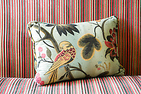 Close-up of floral patterned cushion on a striped sofa