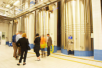 In the winery: A group of visitors in the main blending hall with big stainless steel wine vats for fermentation or blending, the Union Champagne cooperative, also called Champagne de Saint Gall in Avize, Cote des Blancs, Champagne, Marne, Ardennes, France