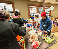 Clients check out with volunteers at the West Side Campaign Against Hunger (WSCAH) a supermarket style food pantry on the Upper West Side neighborhood of New York on Friday, December 19, 2014. The clients get to choose their groceries for themselves and their families. In 2014 WSCAH provided food for over 1.1 million meals for nearly 10,000 families. The supermarket-style distribution promotes self-reliance and empowers the clients. (© Richard B. Levine)