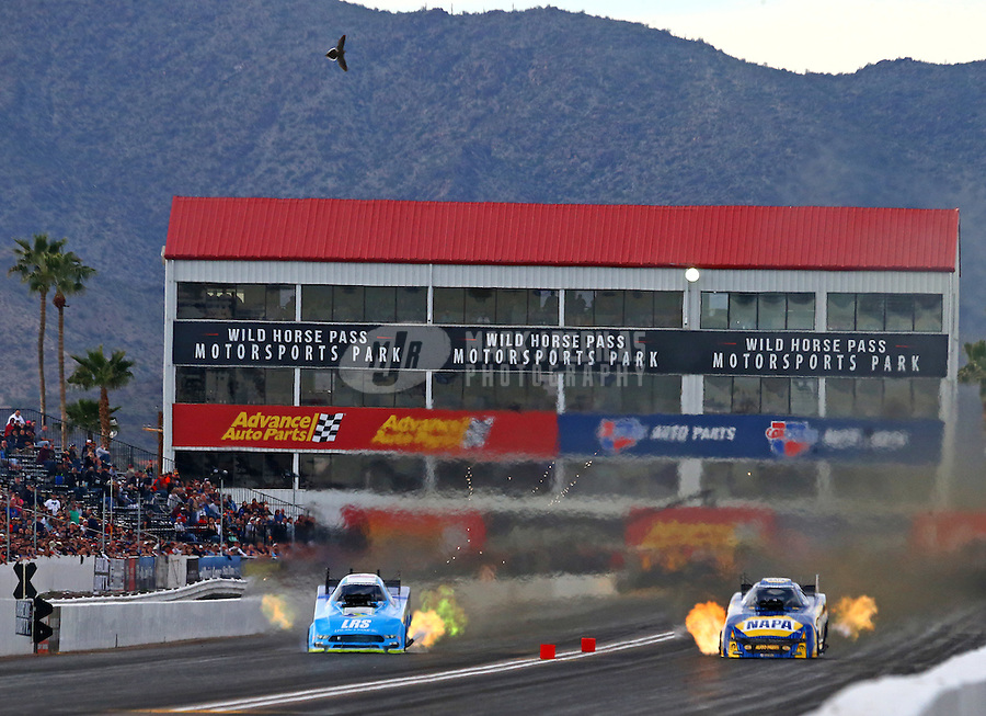 Feb 25, 2017; Chandler, AZ, USA; A bird flies over the track as NHRA funny car driver Tim Wilkerson (left) races alongside Ron Capps during qualifying for the Arizona Nationals at Wild Horse Pass Motorsports Park. Mandatory Credit: Mark J. Rebilas-USA TODAY Sports