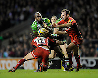 Ugo Monye of Harlequins is tackled by Brad Barritt of Saracens (left) as Charlie Hodgson of Saracens assists during the Aviva Premiership match between Harlequins and Saracens at Twickenham on Tuesday 27 December 2011 (Photo by Rob Munro)