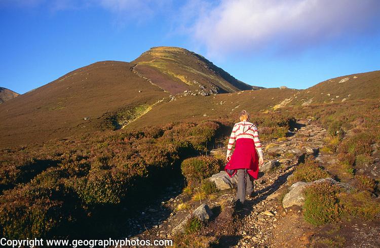 Woman walking up eroded footpath Glen Clova, Cairngorm Mountains, Angus, Scotland