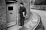 Upper Slaughter, Gloucestershire 1975. England. Postman delivery newspapers in the village.