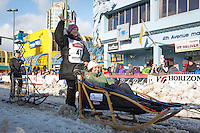 Becca Moore and team leave the ceremonial start line with an Iditarider at 4th Avenue and D street in downtown Anchorage, Alaska during the 2015 Iditarod race. Photo by Jim Kohl/IditarodPhotos.com