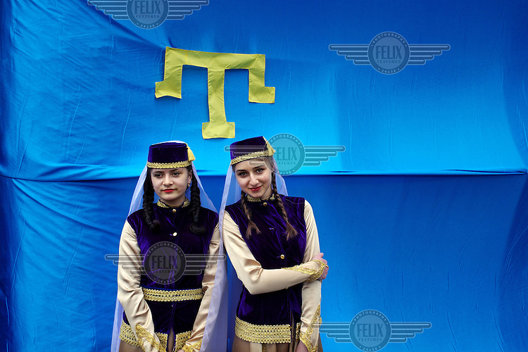 Two young Crimean Tatar girls pose for a photo in front of  the Crimean Tatar flag in the village of Novoalekseyevka during a commemoration ceremony remembering the deportation of Crimea's Tatars 70 years ago. They were deported from the region by the Soviet central authorities in 1944. The deported Crimean Tatars were resettled mainly in Central Asia. Beyond the ex-Soviet borders there are some Crimean Tatars in Romania and Turkey. Russia annexed Crimea in March following a hastily called referendum in which voters overwhelming supported the secession from Ukraine. Many Crimean Tatars opposed the annexation of Crimea and support the central authorities in Kiev.