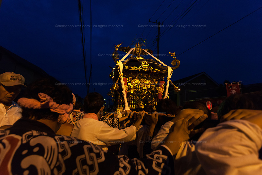 Mikoshi are carried through the streets at night during the Hamaorisai matsuri in Chigasaki, Kanagawa, Japan. Monday July 17th 2017. This festival is celebrated on Marine Day in Japan. Over 40 mikoshi (portable shrines) are paraded through the night to arrive on the coast at Southern Beach where they are blessed in a Shinto ritual before being carried into the waves to be purified.
