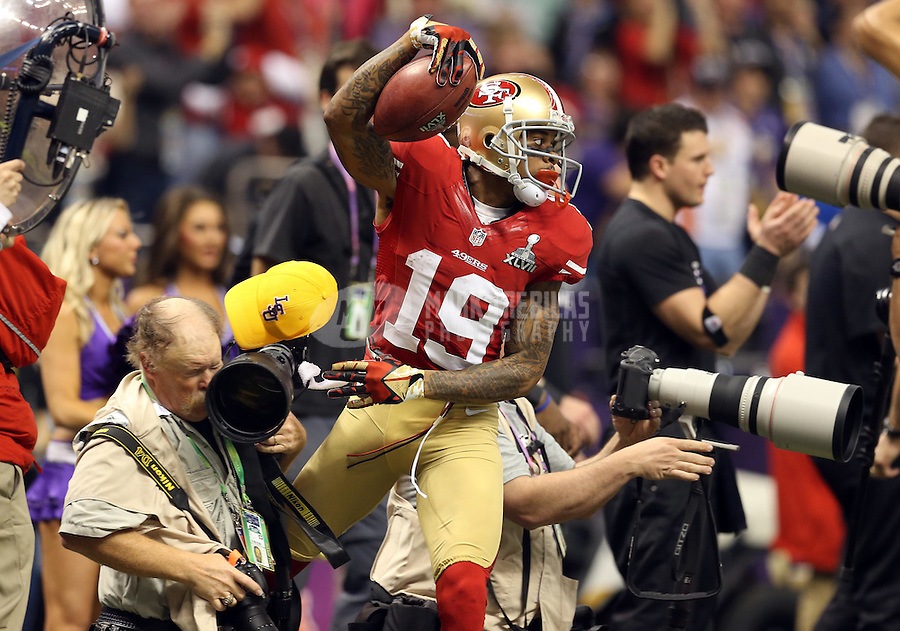 Feb 3, 2013; New Orleans, LA, USA; San Francisco 49ers wide receiver Ted Ginn (19) shoves a photographer's lens out of the way as he heads back to the field in the second half against the Baltimore Ravens in Super Bowl XLVII at the Mercedes-Benz Superdome. Mandatory Credit: Mark J. Rebilas-