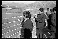 Chinese visitors check their Polaroid instant photos on the Great Wall near Beijing, China, 1985.