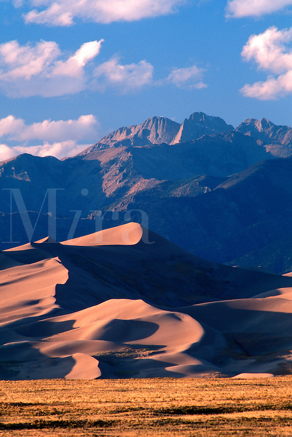 Clouds and blue sky over mountain peaks and golden sand dunes, Great Sand Dunes National Monument, Colorado.