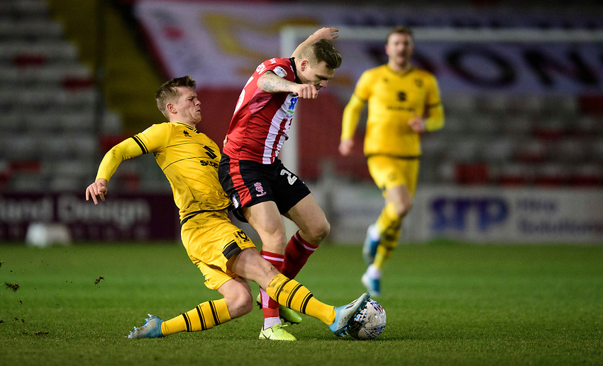 Lincoln City's Harry Anderson is tackled by Milton Keynes Dons' Rhys Healey<br /> <br /> Photographer Chris Vaughan/CameraSport<br /> <br /> The EFL Sky Bet League One - Lincoln City v Milton Keynes Dons - Tuesday 11th February 2020 - LNER Stadium - Lincoln<br /> <br /> World Copyright © 2020 CameraSport. All rights reserved. 43 Linden Ave. Countesthorpe. Leicester. England. LE8 5PG - Tel: +44 (0) 116 277 4147 - admin@camerasport.com - www.camerasport.com