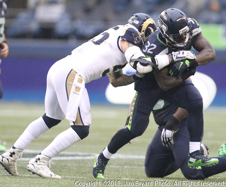 Seattle Seahawks running back Christian Michael (32) gains yards after getting hit by St. Louis Rams linebacker James Laurinaitis (55) at CenturyLink Field in Seattle, Washington on December 27, 2015.  The Rams beat the Seahawks 23-17.      ©2015. Jim Bryant Photo. All Rights Reserved