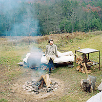 Portrait of designer and artist J Morgan Puett sitting on a bed in a clearing of woodland that surrounds her artists' colony