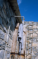 A rustic shower stands at the side of the house where a rope ladder leads up to the flat roof