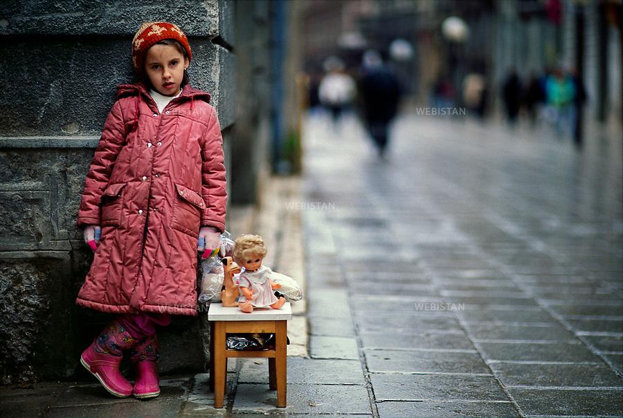 Bosnie. Sarajevo. Décembre 1993<br /> L'air était glacé, la ville respirait au rythme des sursis accordés. Les rues désertes s'animaient parfois de la course folle de celui qui risquait sa vie pour un peu d'eau, pour une miche de pain, sous le regard des snipers. Elle était là, immobile petite touche de couleur dans la grisaille froide de la guerre. Sans un mot, sans un geste, elle vendait ses jouets, témoins d'une vie perdue. Je me suis senti profondément démuni, face à cette injustice de l'Humanité qui contraignait une fillette à vendre ce qu'elle avait de plus précieux, ses compagnons, ses garants de l'enfance. C'était dans Sarajevo assiégée que je l'ai vue lutter en silence.<br /> <br /> Bosnia. Sarajevo. December 1993<br /> The air was chilling, and the city breathed to the rhythm of granted sentence respites. The deserted streets would sometimes come to life as a man ran wild risking his life for a little water or a loaf of bread under the snipers' eyes.<br /> She was standing there, like a motionless color stain in the cold dreariness of war.<br /> Without a word, without a move, she was selling her toys, testimony of a wasted life. <br /> I felt quite helpless facing such human injustice that forced a little girl to sell what was dearest to her, they were her companions, her childhood's guarantors.<br /> I saw her fighting silently in besieged Sarajevo.