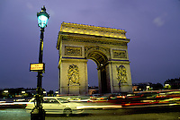 Arc de Triomphe, Paris, France, Europe, Arc de Triomphe at Place Charles de Gaulle illuminated at night in Paris. Traffic passing around the circle.