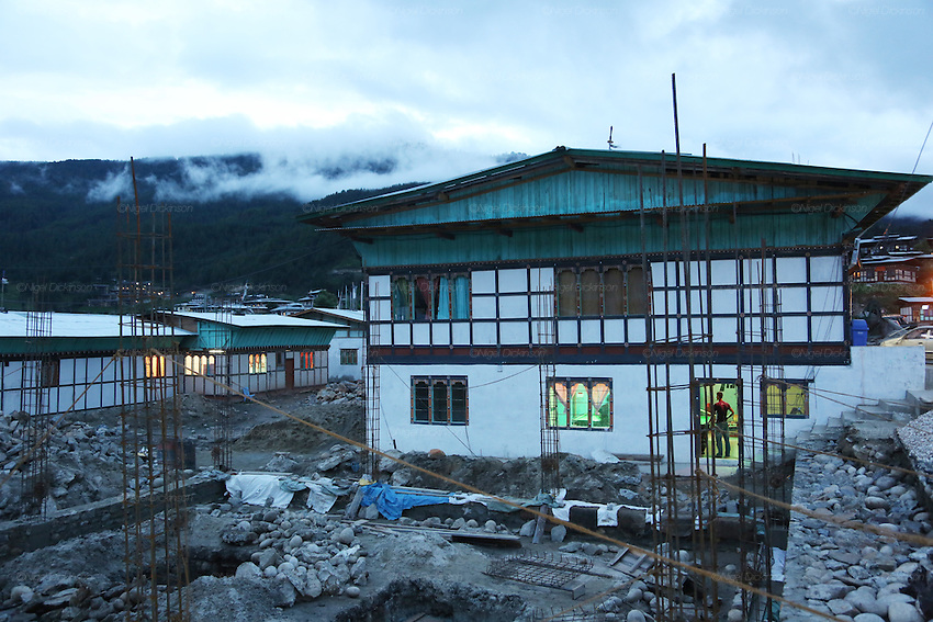 Construction, snooker hall, early evening at Bumthang town, Bhutan..Bhutan the country that prides itself on the development of 'Gross National Happiness' rather than GNP. This attitude pervades education, government, proclamations by royalty and politicians alike, and in the daily life of Bhutanese people. Strong adherence and respect for a royal family and Buddhism, mean the people generally follow what they are told and taught. There are of course contradictions between the modern and tradional world more often seen in urban rather than rural contexts. Phallic images of huge penises adorn the traditional homes, surrounded by animal spirits; Gross National Penis. Slow development, and fending off the modern world, television only introduced ten years ago, the lack of intrusive tourism, as tourists need to pay a daily minimum entry of $250, ecotourism for the rich, leaves a relatively unworldly populace, but with very high literacy, good health service and payments to peasants to not kill wild animals, or misuse forest, enables sustainable development and protects the country's natural heritage. Whilst various hydro-electric schemes, cash crops including apples, pull in import revenue, and Bhutan is helped with aid from the international community. Its population is only a meagre 700,000. Indian and Nepalese workers carry out the menial road and construction work.