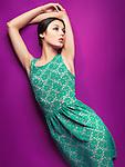 Young beautiful woman wearing vintage style green dress on purple background. Fashion photo.