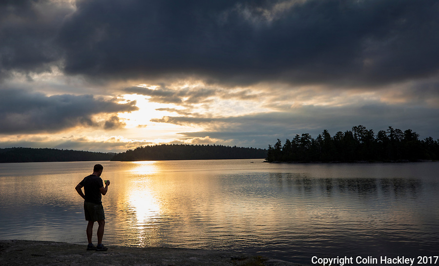 BWCA, MN, 8/1/17-A camper watches as morning sun warms the clouds over Iron Lake in the Boundary Waters Canoe Area. <br />
