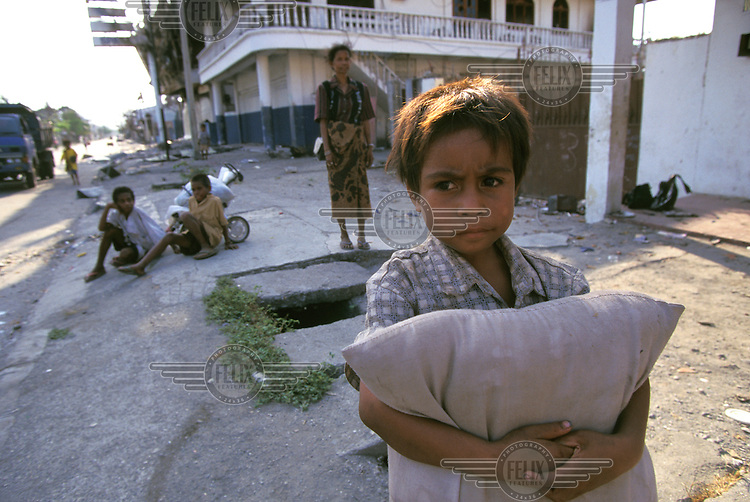 ©ÊJim Holmes / Panos Pictures..Dili, East Timor...Children scavenging on the streets and in destroyed buildings looking for food.