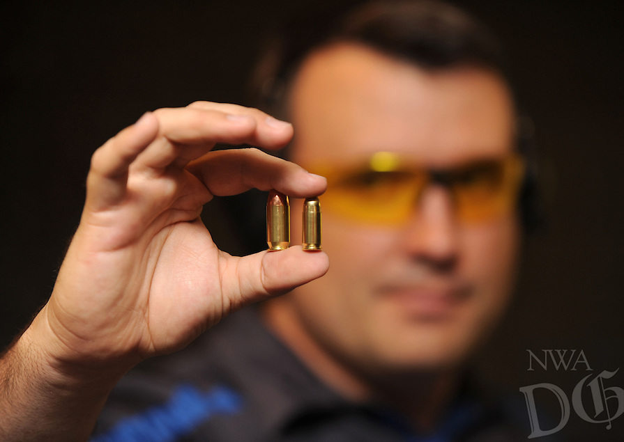 NWA Democrat-Gazette/ANDY SHUPE<br /> Everett Deger, marketing director for Walther Firearms in Fort Smith, Wednesday, Aug. 26, 2015, holds a .45-caliber round (left) and a traditional 9mm round on the right. The longtime German gunmaker has designed the PPQ 45 .45-caliber pistol for the American market.