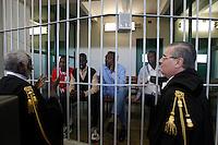 Gli avvocati Douglas Duale, sinistra, e Massimo Mercurelli, destra, parlano ai presunti pirati somali, da sinistra, Mohamed Isse Karshe, Abdi Hassan Mahamur, Ahmed Malimed Ali ed Abdullahi Ali Ahmed, accusati dell'attacco alla nave portacontainer italiana Montecristo, durante la prima udienza del processo presso la III Corte d'Assise a Roma, 23 marzo 2012. La nave, assaltata il 10 ottobre 2011 al largo della Somalia, venne liberata il 15 ottobre dai Royal Marines britannici con l'ausilio di una nave militare statunitense..Lawyers Douglas Duale, left, and Massimo Mercurelli, right, talk to Somali allegedly pirates, from left, Mohamed Isse Karshe, Abdi Hassan Mahamur, Ahmed Malimed Ali and Abdullahi Ali Ahmed, during the opening audience for the assault to the Montecristo container ship, in Rome, 23 march 2012. The ship was attacked on 10 october 2011 and freed by US navy and British Royal Marines on 15 october..UPDATE IMAGES PRESS/Riccardo De Luca