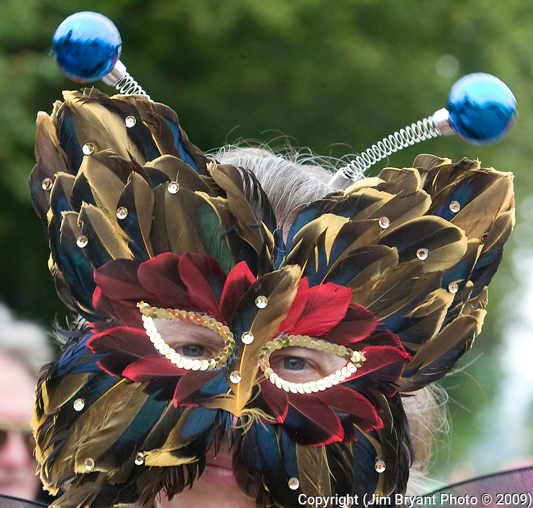 Roberta Nelms wears a feathered mask in the 21st annual Summer Solstice Parade held Saturday, June 20, 2009 in Seattle, Wa.The parade was held Saturday, bringing out painted and naked bicyclists, bands, belly dancers and floats. (Jim Bryant Photo © 2009)