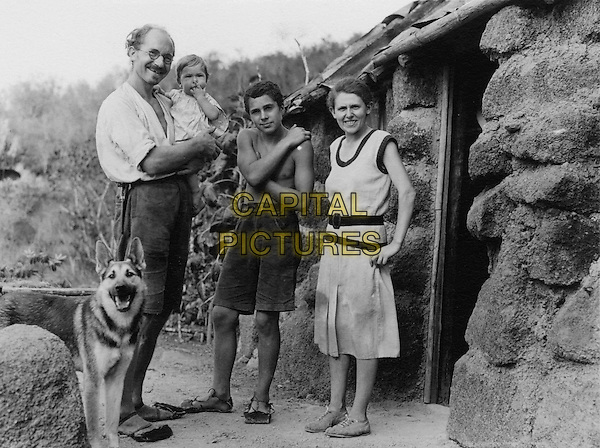Heinz Wittmer holding baby Rolf and standing beside his son Harry and wife Margret with their dog Lump. In front of their first real house on Floreana Island<br /> in The Galapagos Affair: Satan Came to Eden (2013) <br /> *Filmstill - Editorial Use Only*<br /> CAP/NFS<br /> Image supplied by Capital Pictures